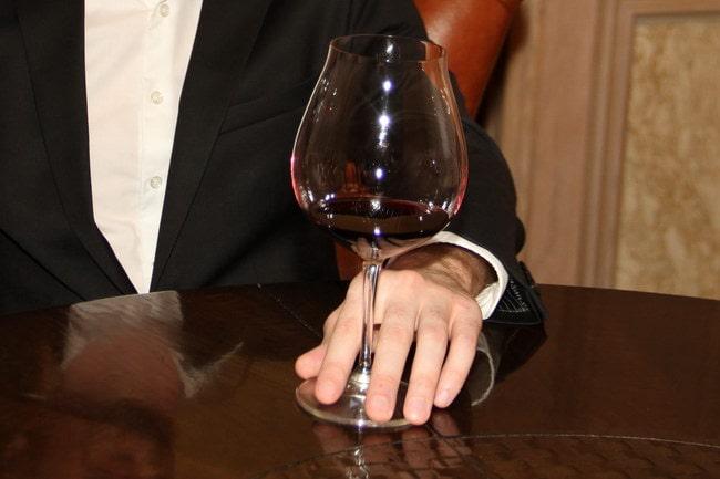 Прижать бокал к столу, чтоб не расплескать при кручении